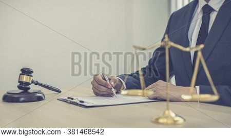 Judge or a lawyer works documents in the courtroom and analyze the various laws for justice and accu