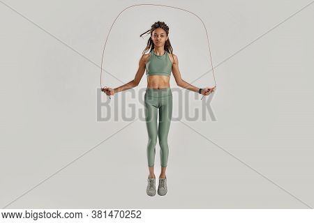 Jump Everyday. Full Length Shot Of Young Sportive Mixed Race Woman In Sportswear Doing Exercises Wit