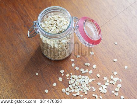 Raw Oatmeal In A Jar On The Table In The Kitchen, Scattered Oatmeal