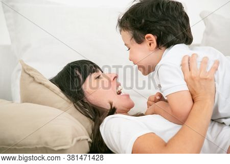 Young Brunette Mother Lying On Pillow And Talking With Cute Son. Adorable Little Boy Looking At Long