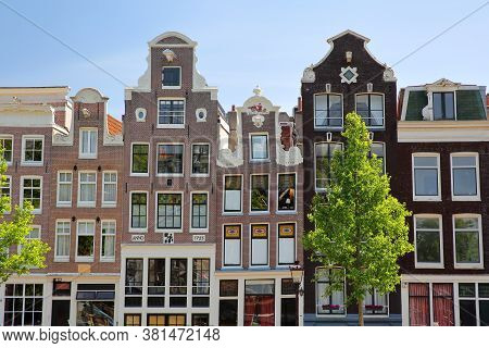 Crooked Heritage Buildings Located Along Singel Canal In Amsterdam, Netherlands