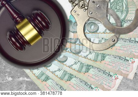 20 Thai Baht Bills And Judge Hammer With Police Handcuffs On Court Desk. Concept Of Judicial Trial O