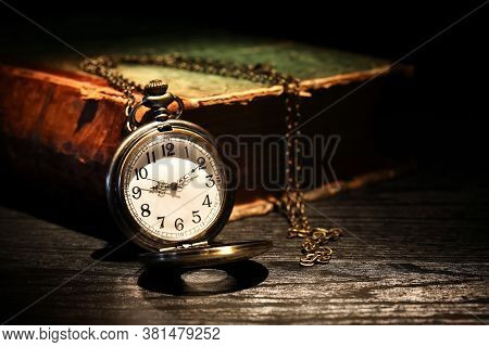 Old Pocket Watch Near Old Book On Dark Background