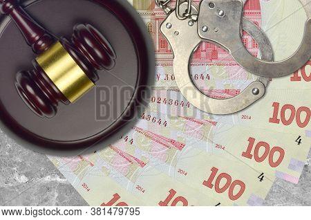 100 Ukrainian Hryvnias Bills And Judge Hammer With Police Handcuffs On Court Desk. Concept Of Judici