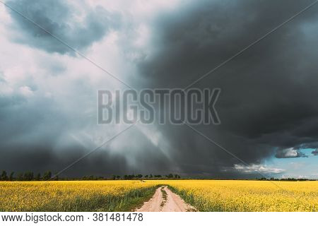 Dramatic Rain Sky With Rain Clouds And Sunrays On Horizon Above Rural Landscape Camola Colza Rapesee