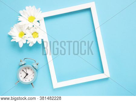 Square White Frame With White Flowers And Blue Alarm Click On Blue Background. View Top. Check Up Ti