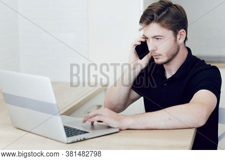 Young Man Working At Home On A Laptop Talking On A Cell Phone, Sitting At Desk. Work At A Distance D