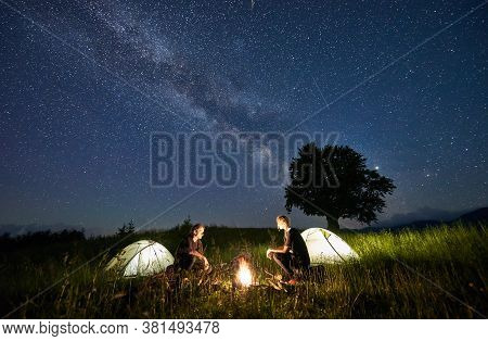 Beautiful View Of Night Starry Sky Over Meadow With Hikers Near Illuminated Camp Tents. Tourists Sit