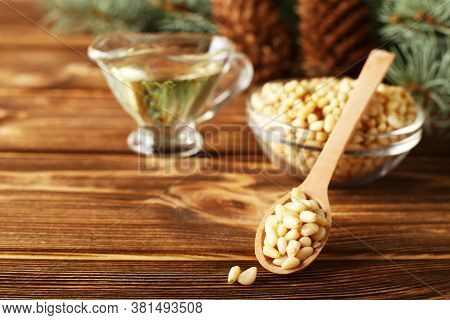 Cedar Products: Pine Nuts, Cedar Oil, Cones, Brunches On A Wooden Broun Background.