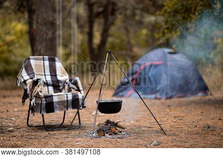 Relaxing And Preparing Food On Campfire In Camping, Autumn Rest In Forest