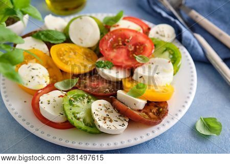 Caprese Salad With Mozzarella, Colored Tomatoes And Fresh Basil.