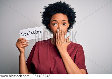 Young African American afro politician woman with curly hair socialist party member cover mouth with hand shocked with shame for mistake, expression of fear, scared in silence, secret concept