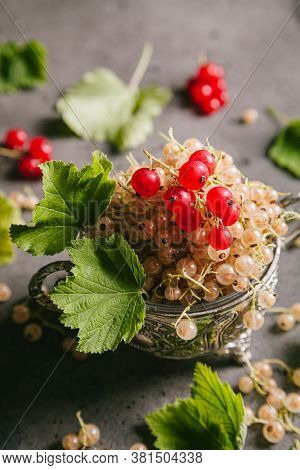 White Currant And Red Currant With Leaves In A Metal Vintage Bowl On A Gray Background. Close Up, Co