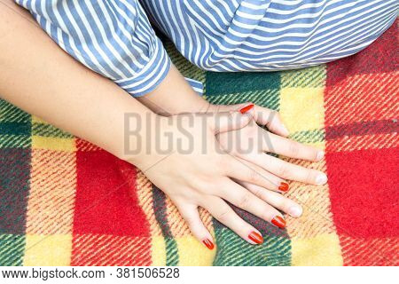 Happy Couple Of Young Women Hold Hands. Two Young Women Sitting On A Bright Plaid Blanket And Hold H