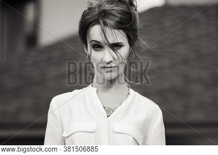 Sad young business woman on city street Stylish fashion model in white shirt with bun updo hairstyle