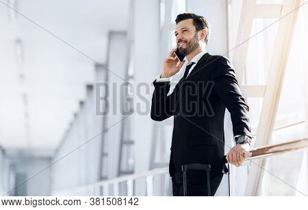 Happy Wealthy Businessman Standing In Airport, Talking On Phone, Having Business Trip, Panorama With