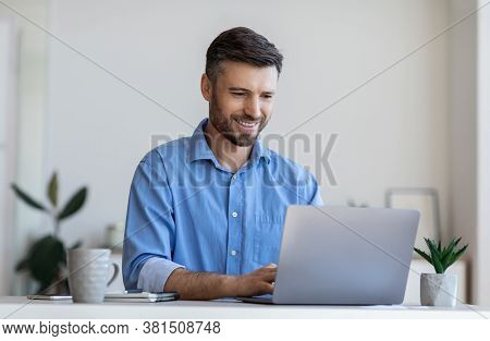 Handsome Male Entrepreneur Working On Laptop At Desk In Modern Office, Using Computer At Workplace,