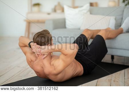 Workout At Home For Body Care. Muscular Guy Shirtless, Doing Exercises For Press, Putting Feet On So