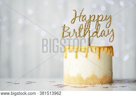 Golden birthday cake with happy birthday sign