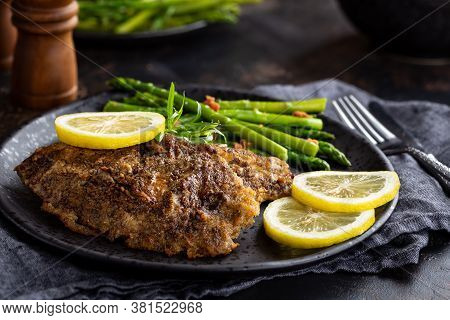 Baked Tilapia Fish Fillets With Lemon Slices And Asparagus On A Black Plate