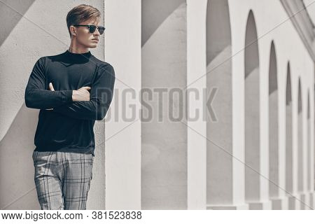 Art fashion portrait. Handsome young man model in black pullover and black sunglasses posing next to white columns in the old town. Men's style, beauty.