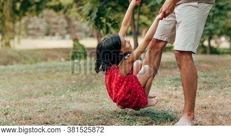 Playful Daughter With His Father Swinging On Daddy's Leg Outdoors. Сute Little Girl Playing With Her