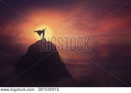 Conceptual Sunset Scene, Superhero With Cape Standing Brave On Top Of A Mountain Looks Determined At