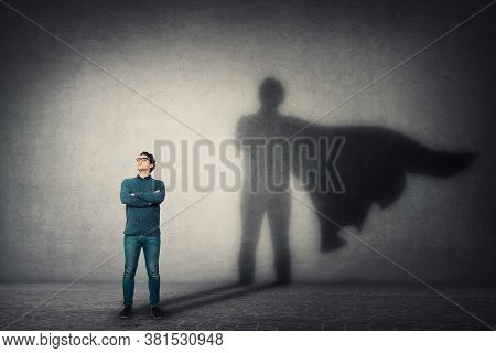 Brave Man Keeps Arms Crossed, Looks Confident, Casting A Superhero With Cape Shadow On The Wall. Amb