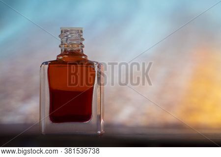 A Bottle Of Aurasoma With A Red Essence Against An Abstract Background.