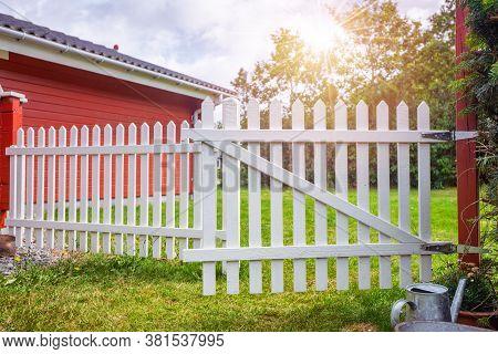 White Picket Fence I An Idyllic Garden. Red Summer Cabin Behind A White Gate. Countryside Garden In