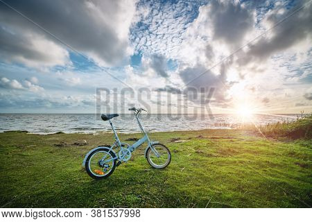 Foldable Bike By The Ocean At Sunset. Active In Nature By The Sea Watching The Sunset. Blue Bicycle