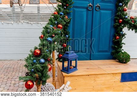 Christmas Decor Of The Front Door. Blue Door, Railing Of The Stairs Are Decorated With Fir Branches