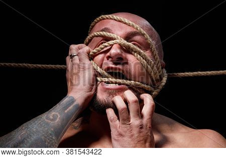 Photo Of Binded Bald Man Trying Tear The Rope On Face