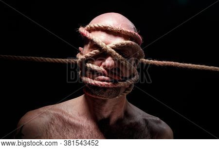 Photo Of Binded Bald Adult Man With Rope On Face