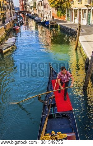 Venice, Italy - April 22, 2019 Gondola And Gondolier In Colorful Small Canal Creates Beautiful Refle