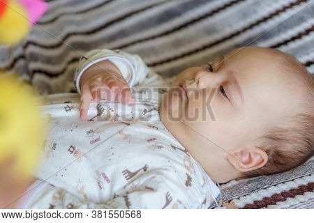Cute Baby Girl On Colorful Playmat And Gym, Playing With Hanging Rattle Toys. Kids Activity And Play