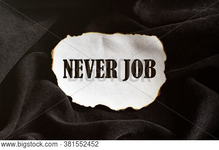 Burnt White Piece Of Paper With Text Never Job On A Black Fabric Background