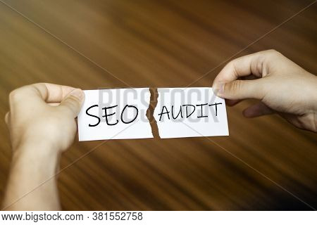 Torn Paper With Text Seo Audit In Male Hands On Wood Background
