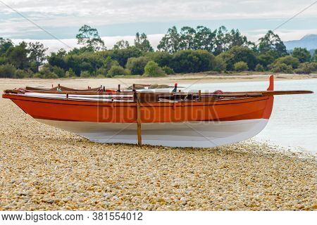 Orange Wooden Fishing Boat On A Deserted Island Beach