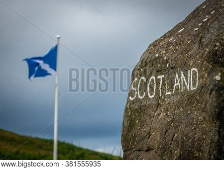 A Stone Sign At The Scottish Border With A Scotland Flag In The Distance