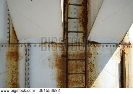 An Old Rusted Silo Photographed In A Port Area In Summer