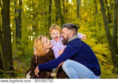 Happy Smiling Parents With Little Son In Autumn Park. Autumn Family. Family Parenthood And People Co