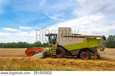 Combine Harvester Harvests Ripe Wheat In Field, Against Of Trees And Beauty Blue Sky With Clouds. Re