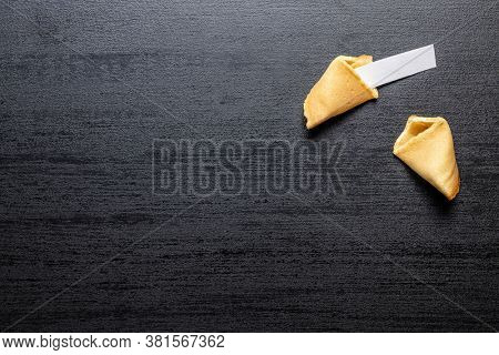 Chinese lucky cookies. Fortune cookies on black table. Top view.