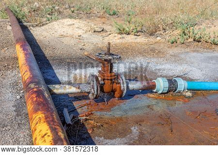 Old Water Valve. An Rusty Water Valve In A Puddle Of Flowing Water. Large And Rusty Faulty Leaking V