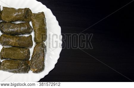Stuffed Grape Leaves On White Plate On Dark Wooden Background With Copy Space. Famous Traditional Mi