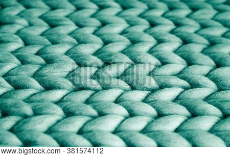 Background. Knitted Fabric Made Of Turquoise Merino Wool. Large Weave. Pattern Of Pigtails.