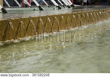 Photo Of The Bottom Tier Of A Water Fountain With Water Pouring Through Repetitive Grooves.