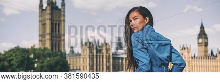 London city Europe travel destination Asian beauty woman at Westminster Houses of Parliament panoramic banner . Autumn holiday lifestyle blue rain coat for fall.