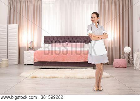 Beautiful Chambermaid Near Bed In Hotel Room